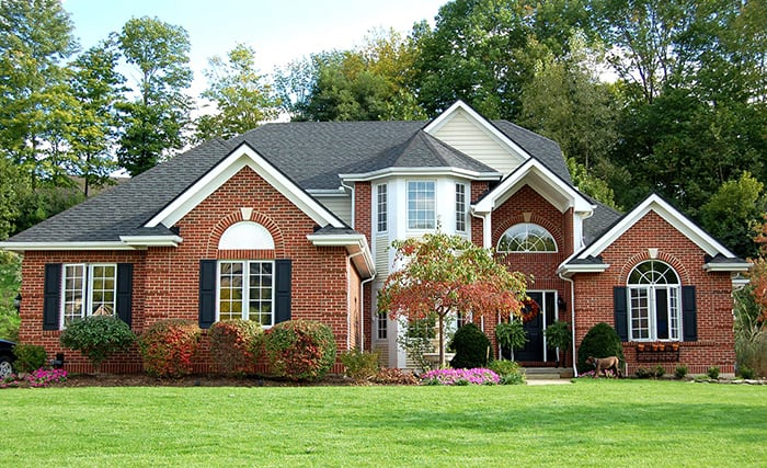 A large residential house with traditional landscaping and lawn. This type of garden landscaping is an ecological disaster.